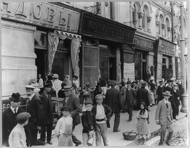[Milk line in Russian city; women and children in long line waiting to buy milk; girl selling apples]