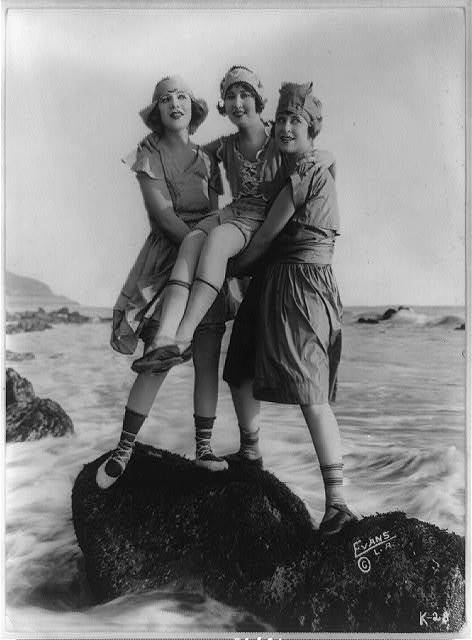 [Myrtle Reeves, Lillian Langston, and Edith Roberts posed on rock in water for Mack Sennett Productions] / Evans, L.A.