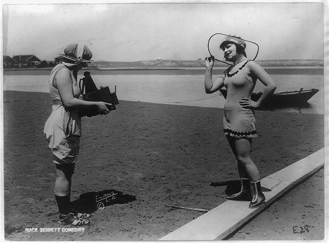 [Roxy McGowan and Mary Thurman in bathing suits, with one taking the other's picture on beach, posed for Mack Sennett Productions] / Evans Studio, L.A.
