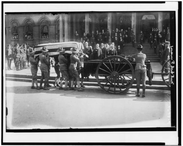 [Soldiers loading flag-draped casket of former New York City mayor John Purroy Mitchel onto wagon, with Theodore Roosevelt and other officials holding their hats in respect]