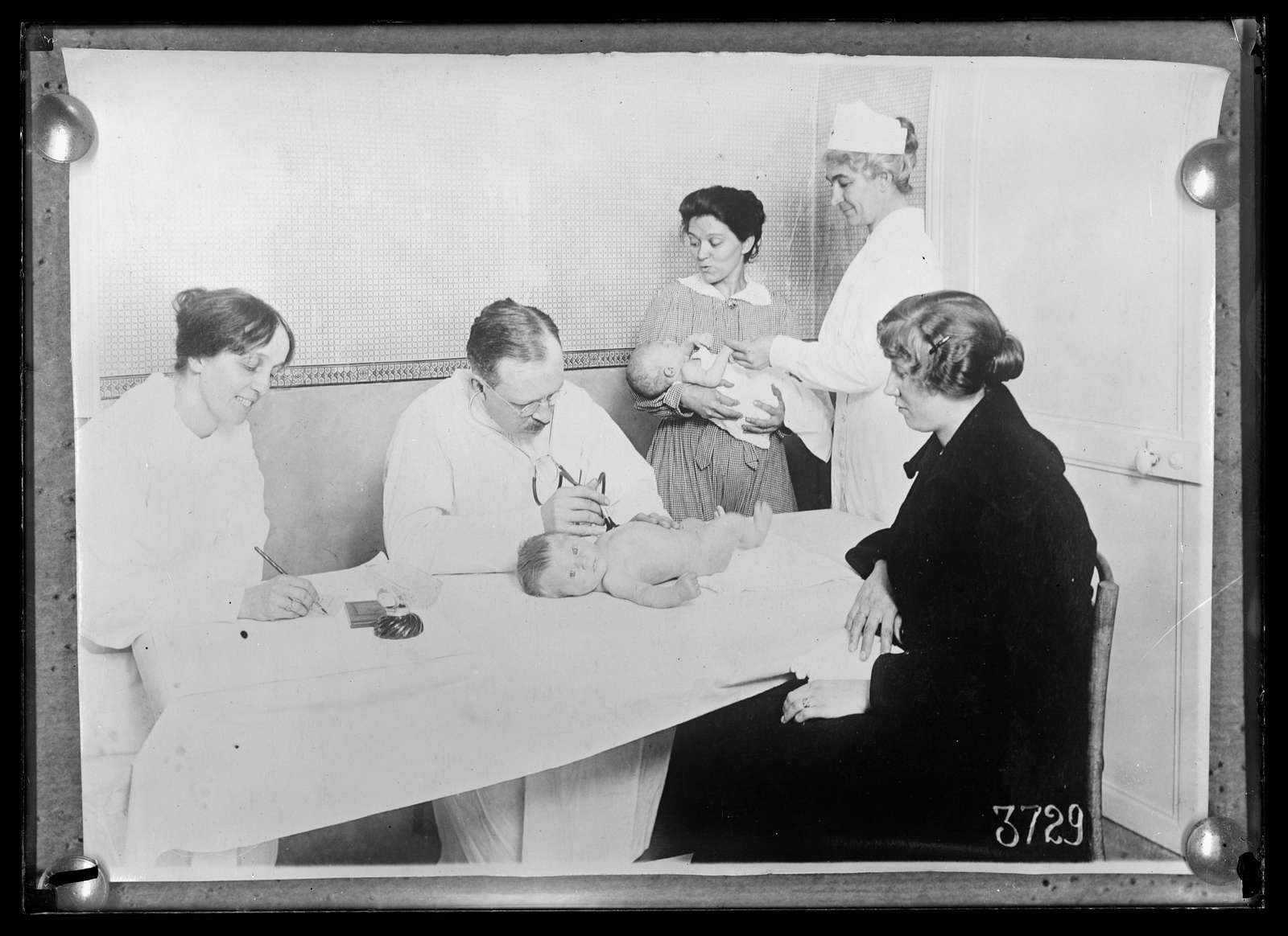 The mothers in the poorer quarters of Paris appreciate the opportunity to bring their babies to the American Red Cross Children's Dispensaries which have been established in many different neighborhoods. The picture shows Dr. Baldwin examining a baby at the dispensary 35 Rue Dareay, Paris