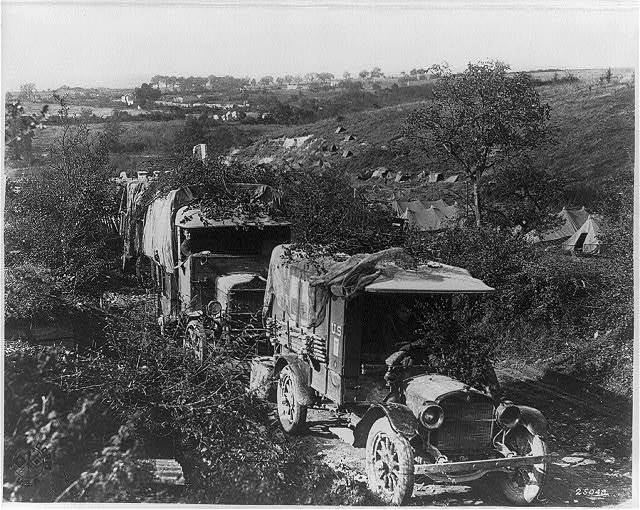 [U.S. Army in France: Camouflaged trucks in foregrd.]