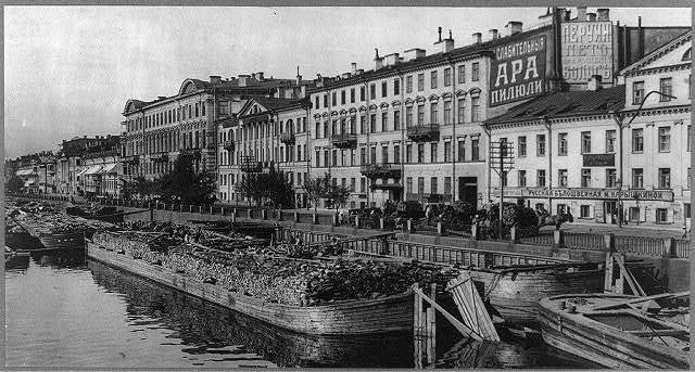 [Wood being loaded on wagons from canal boats on the Fontanka River, St. Petersburg, Russia]