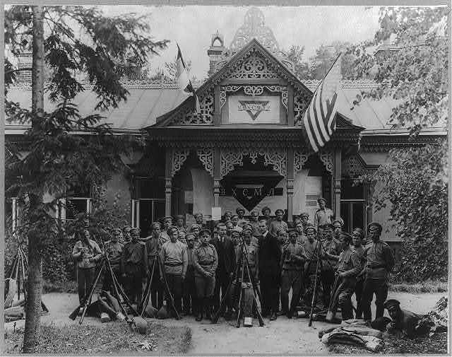 World War I: Russian soldiers with two men (not in uniform) in front of YMCA facility in a Moscow suburb, which was started by Jerome Davis and Wheeler of the American Y.M.C.A.