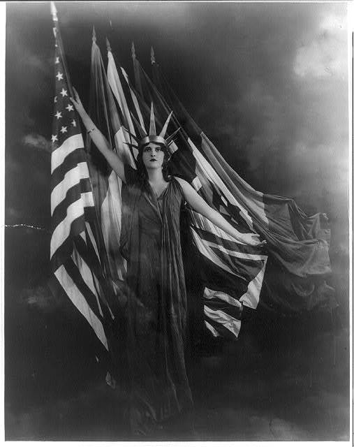 [Young woman posed with flags of the Allied nations]