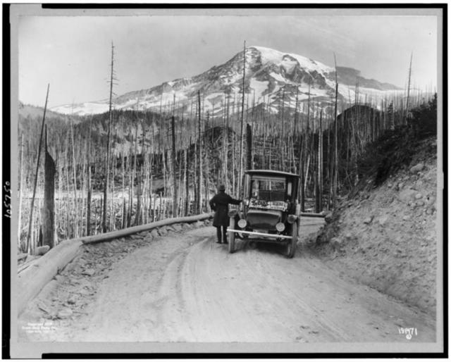 [A Detroit Electric automobile stopped on road by burnt-over land, with snow-covered mountain in background, Washington]