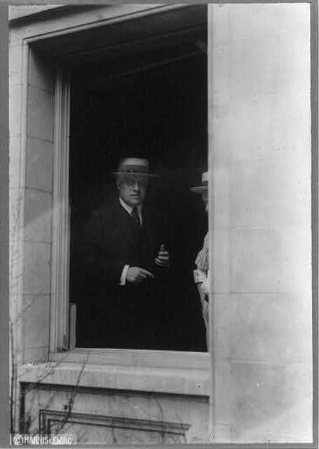 [Attorney General Alexander Mitchell Palmer, half-length portrait, standing, facing slightly right; seen through the window of his home at 2132 R. Street, N.W., Washington, D.C., after it was bombed on June 2, 1919]