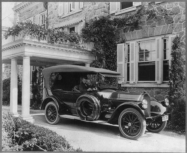 Automobile owned by Mrs. Charles W. Richardson in driveway with driver at the wheel, Washington, D.C.