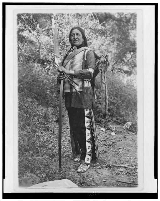 [Chief Standing Bear (possibly Luther Standing Bear) full-length portrait, standing, facing slightly left, holding bow and arrows]