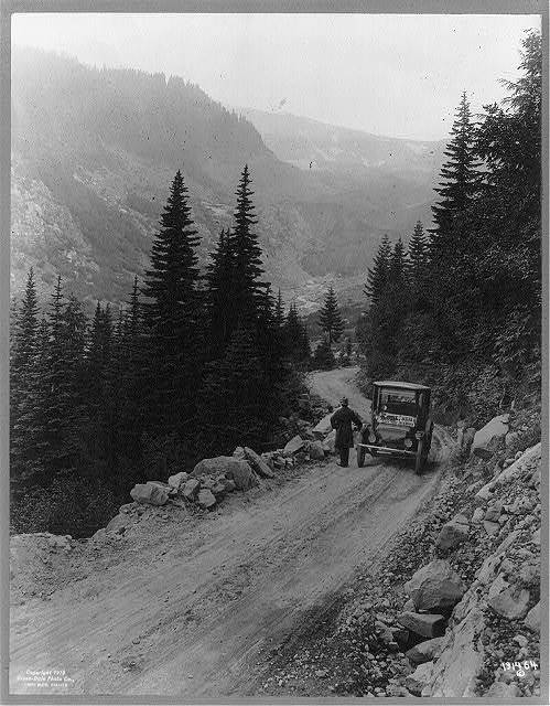 "[""Detroit Electric"" auto on promotional tour through mountains from ""Seattle to Mt. Rainier"": Man standing in front of auto, which is parked on mountain road]"
