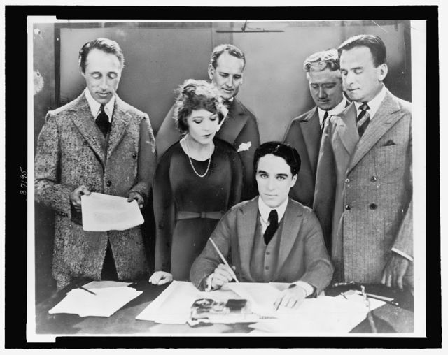 [D.W. Griffith, Mary Pickford, Charlie Chaplin (seated) and Douglas Fairbanks at the signing of the contract establishing United Artists motion picture studio]