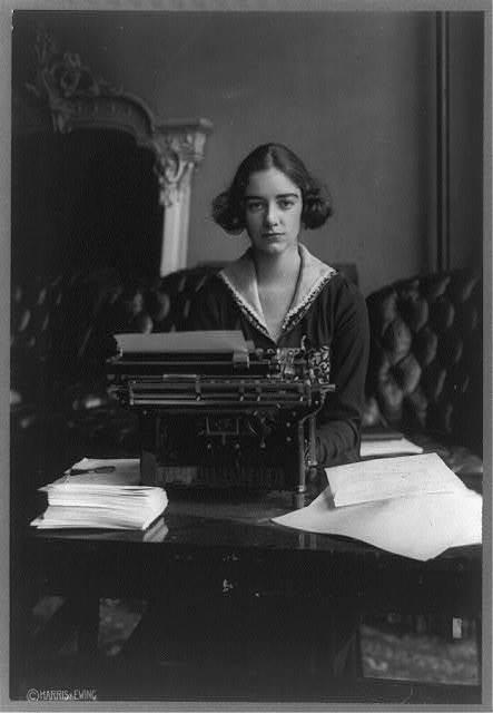 [Flora Payne Whitney Miller, three-quarter length portrait, seated at typewriter, facing front]