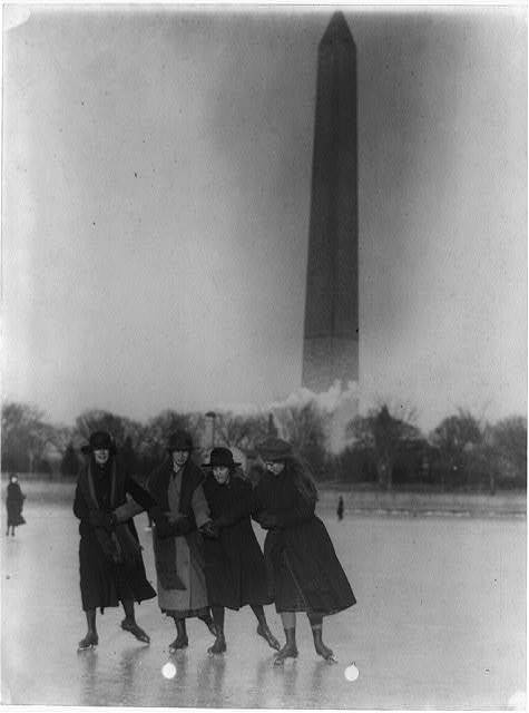 [Four girls ice skating, with Washington Monument in background]