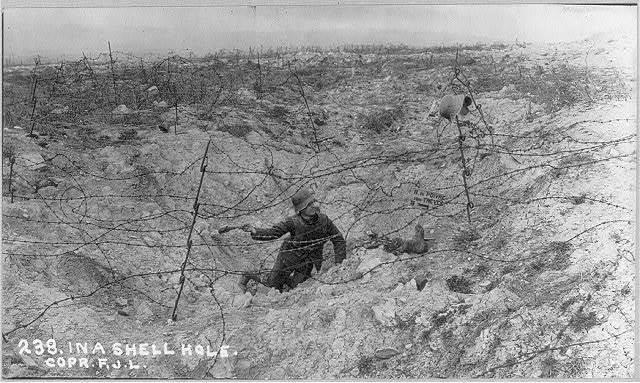 [German soldier in shell-torn field]