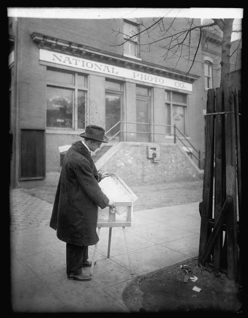 [Herbert E. French, getting a paper from a paper box outside the National Photo Co. Building, Washington, D.C.]