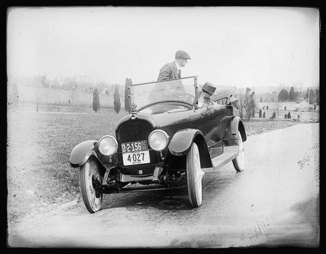 [Man and Woman in automobile with DC and Maryland plates], 1919