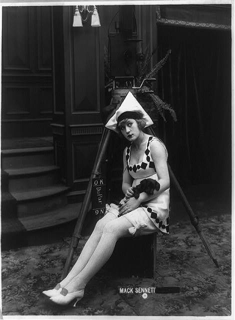 [Marvel Rea of Mack Sennett comedy films seated, in front of motion picture camera, full-length portrait, holding puppy]