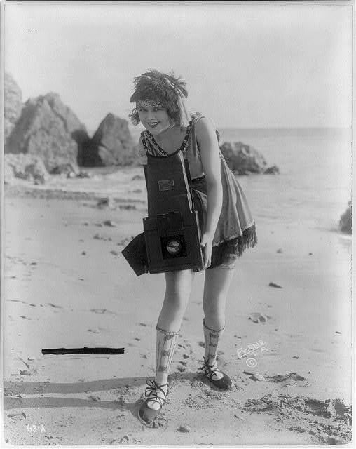 [Myrtle Lind. A young woman posed with a Graflex camera on a beach]