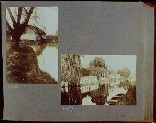 Reference prints, 1919-1920, numbers 2133-2377. Stream flowing by stone building and large tree; Wooden buildings lining river bank with boat in foreground