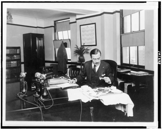 [R.G. Cholmeley-Jones, Director of the War Risk Bureau, eating lunch at his desk]