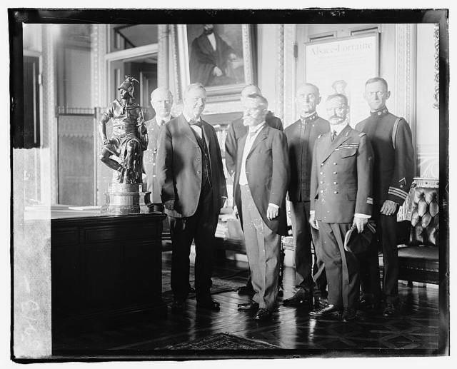 Secretary of the Navy, Josephus Daniels being presented a bronze statue by French Ambassador Jean Jusserand, for the U.S.S. Seattle, which escorted troop-ships to France. Front row, L. to R.: Secty. Daniels, Ambassador Jusserand, Capt. Sainte Seine; Back row, L. to R.: Adm. Wilson, Rear Adm. Niblack, Rear Adm. McKean, Com. Foote