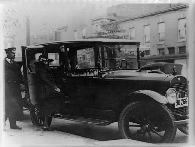 [Woman getting into back seat of car as chauffeur holds door, Washington, D.C., area]