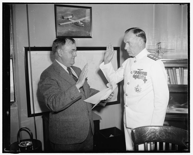 New Chief of Naval Aeronautics takes oath. Washington, D.C., June 1. The newly appointed Chief of Bureau of Aeronautics, U.S. Navy, Capt. John H. Towers, right, being administered the oath of office today by John B. May, Chief Clerk of the Navy Department. The promotion automatically carries with it the rank of Rear Admiral for the new chief, Capt. Towers was one of the pilots of the NC 4 on the massed flight across the Atlantic in 1919