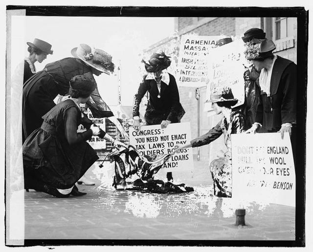 [A group of women carrying signs against America's support of the English against the Irish, and burning a flag(?) on the sidewalk, June 3, 1920