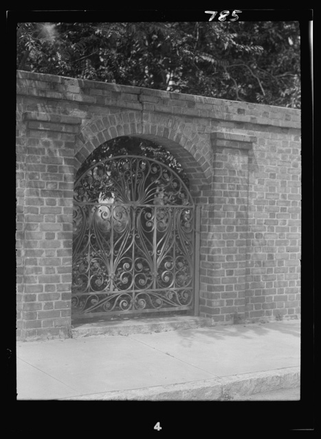 Arched wrought iron gate in free-standing brick wall, New Orleans or Charleston, South Carolina