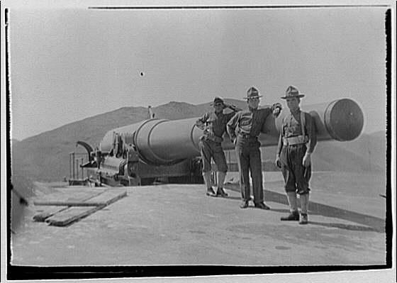 """Artillery gun. Three men in uniform leaning on 12"""" C.A.C. Barbatt carriage gun ar Fort Baker"""