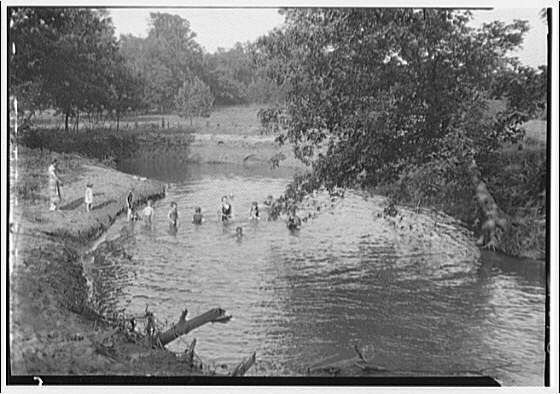 Bathing children in old swimming hole. Distant view of bathing children at swimming hole