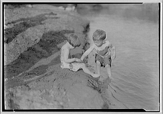 Bathing children in old swimming hole. Two children near bank at swimming hole II