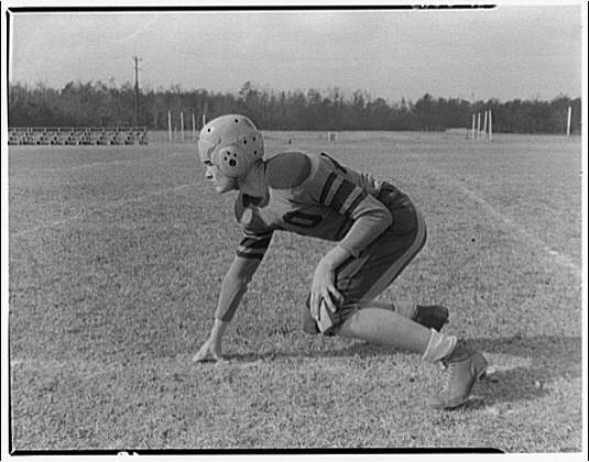 Charlotte Hall Military Academy. Football player, in starting position, profile