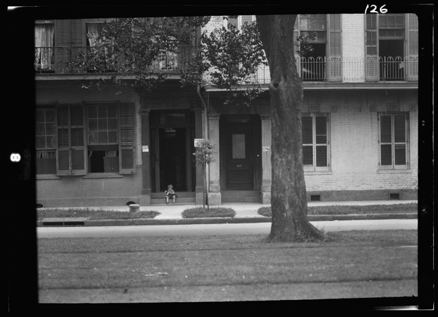 Child holding a dog sitting on steps of a boarding house, New Orleans or Charleston, South Carolina
