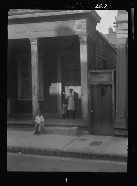 Child sitting on steps by a sidewalk and a woman and child standing at the doorway to a house, New Orleans or Charleston, South