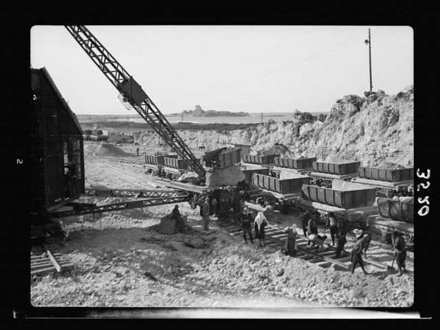 Construction of the Haifa harbour. The Athlit quarries. Loading a train. Athlit ruins in back[g]round