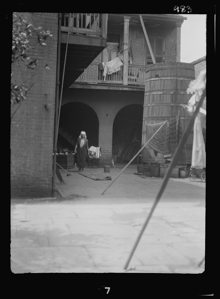 Courtyard with cistern and woman cleaning, New Orleans