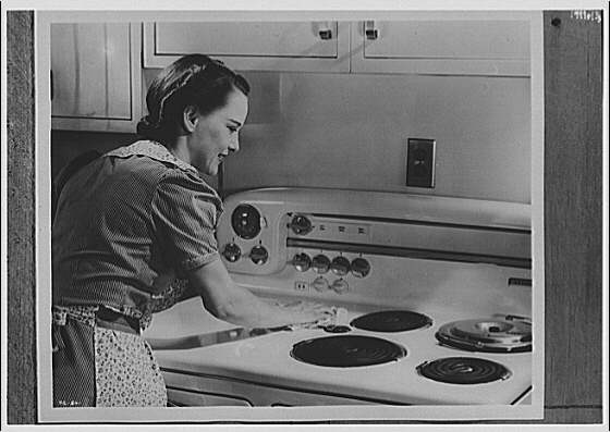 Electric Institute of Washington. Woman cleaning top of stove