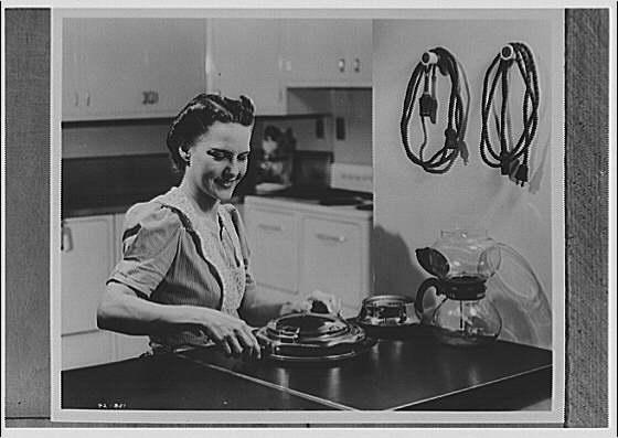 Electric Institute of Washington. Woman preparing something in kitchen