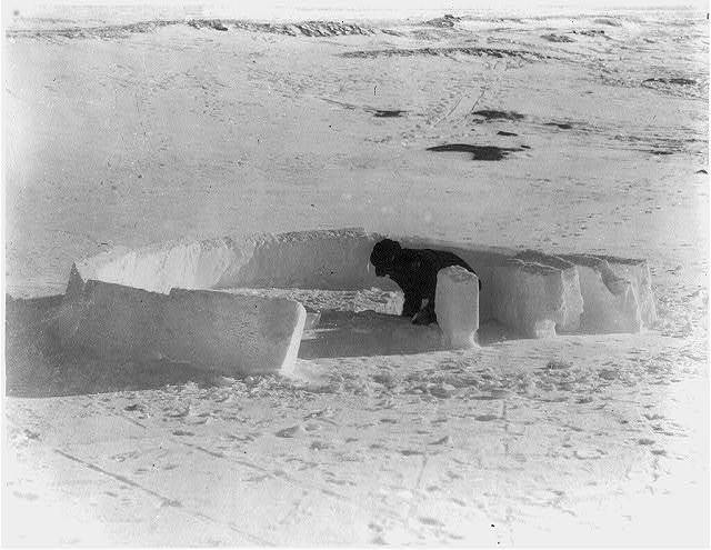 [Eskimo building an igloo; completing the first layer of ice blocks]