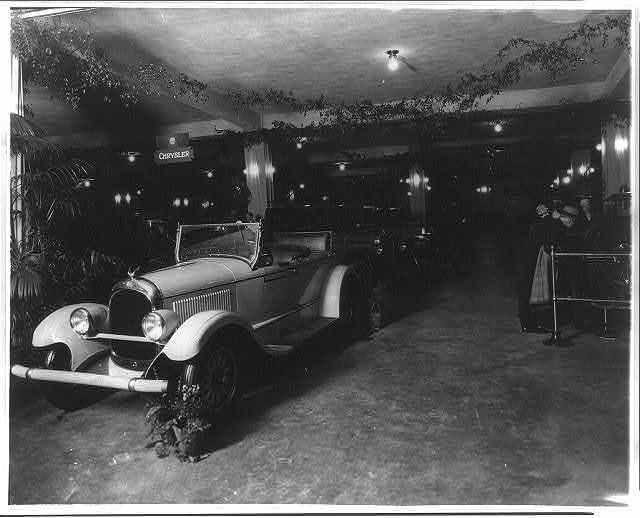 [Exhibits at an unidentified auto show, probably in Washington, D.C., Chrysler convertible in foreground]