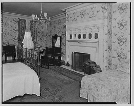 Fairmount School, 1711 Massachusetts Ave. Room at Fairmount School with fireplace, brass bed and other furniture