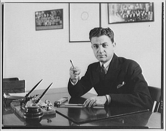 Gas company advertising photographs. Man seated at desk pointing pencil II