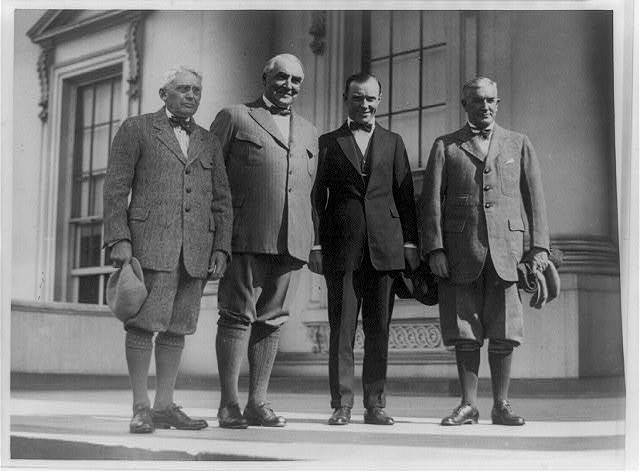 [Group portrait of, standing left to right: Frank Billings Kellogg, Warren G. Harding, Chick Evans (a golfer), and Henry Prather Fletcher; three are wearing knickers]