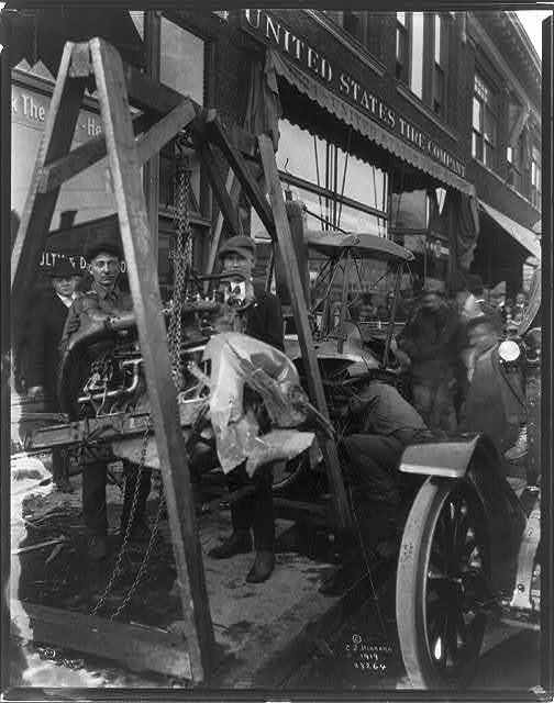[Hoisting motor from airplane which crashed in downtown Minneapolis, Minn., in front of store, 1919]