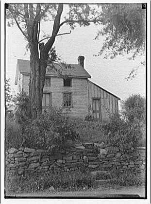 Home in Maryland. Wood house with stone wall and tree