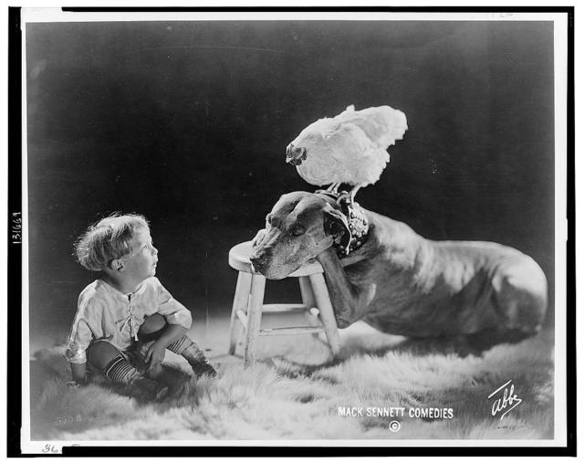 [Large dog resting front paws and head on footstool, chicken perched on dog's collar, small child seated on fur rug gazing at them] / Abbe.