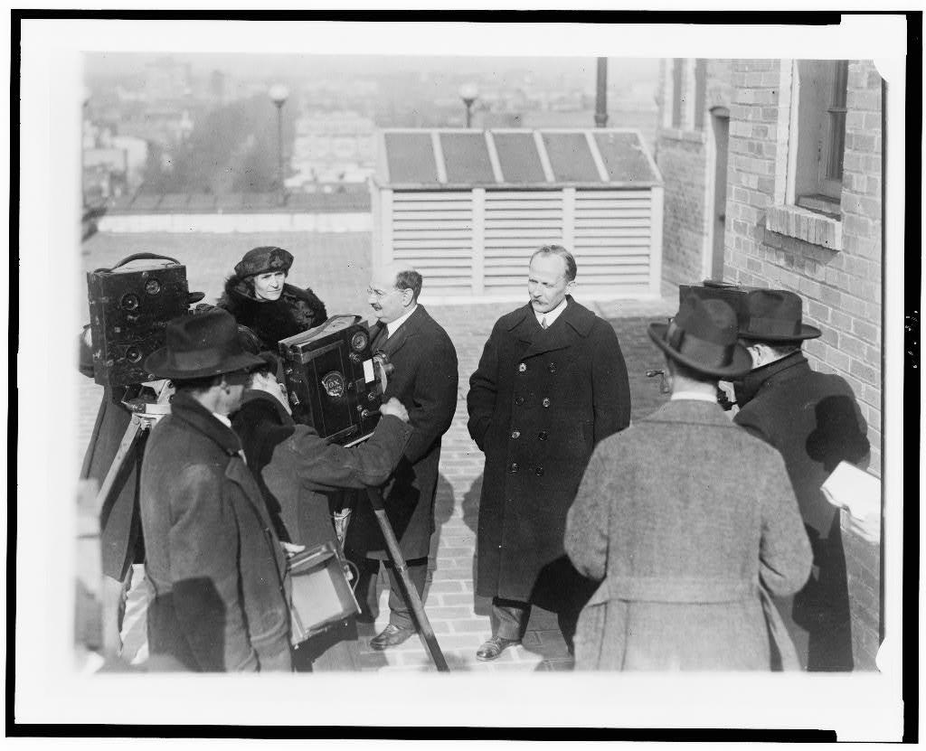 [Ludwig Martens (right), representative of the Soviet government, with his secretary, Mr. S. Nuorteva (left), and Madam Nuorteva, posed on roof, for motion picture camera crew]