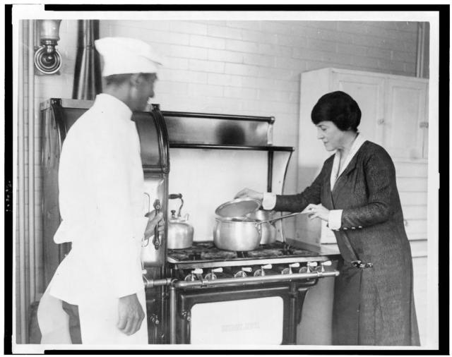 [Mary Roberts Rinehart, lifting lid of pot on stove, and chef standing alongside]