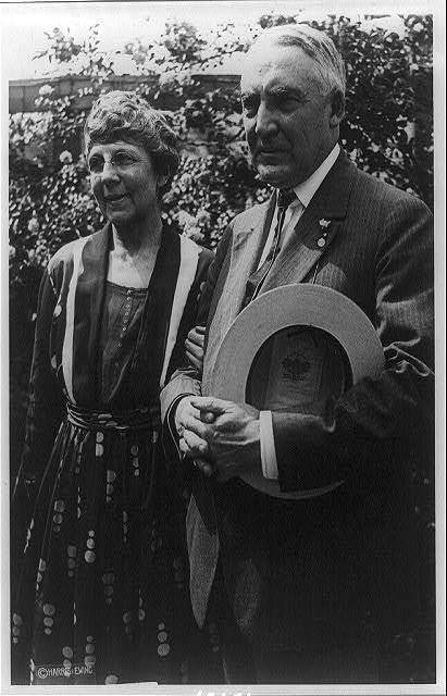 [Mr. and Mrs. Warren G. Harding standing, three-quarter length, in front of rose? bush. Harding is holding his hat in his folded hands]